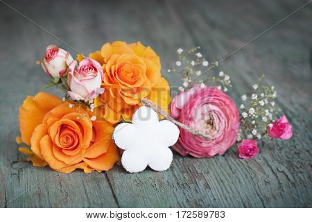 Flower decoration for a small message on an old shabby wooden table