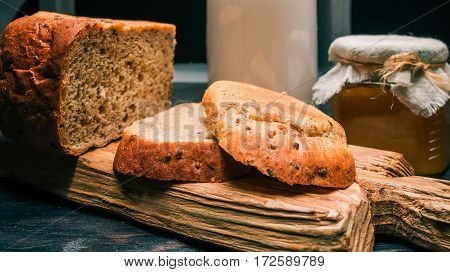 Wholemeal bread loaf, cut toasts and honey on rustic wood board