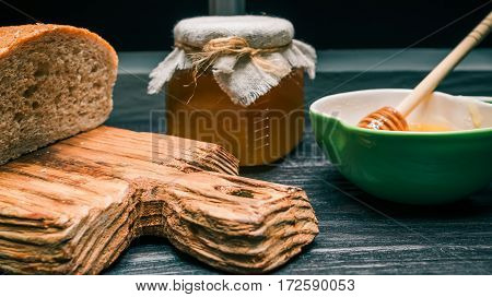 Wholemeal bread and honey with dipper on rustic wood board