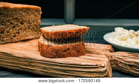 Wholemeal bread loaf, cut toasts and farmer cheese on rustic wood board