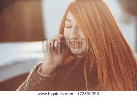 red-haired girl talking on the phone in the winter