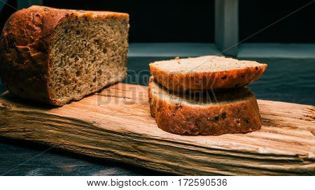 Wholemeal bread loaf and toasts on rustic wood board