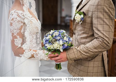 The groom in a suit and the bride in a wedding dress holding hands with each other. Loving couple with a wedding bouquet of blue and white flowers in the church. Wedding boutonniere