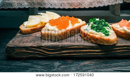 Wholemeal bread sandwiches topped with farmer cheese and colorful snacks and served on rustic wood board