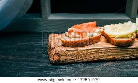 Sandwiches of wholemeal bread with cottage cheese. Colorful fresh fruit toppings. Served on rustic wooden board
