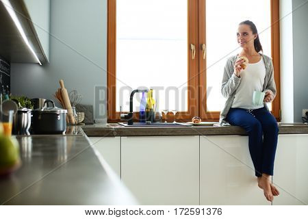 Young woman with cup and cakes sitting in kitchen