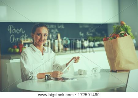 Young woman planning expenses and paying bills on her kitchen