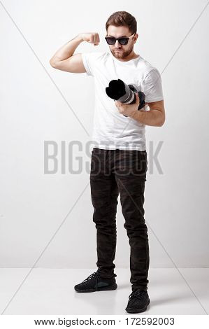 young successful professional photographer in white t-shirt use digital camera with long lens. photographer ready to shoot