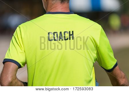 back of a coach's bright green color shirt with the word Coach written on it