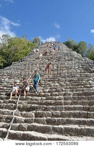 Coba Mexico - January 19 2017: Tourists climbing Temple at Coba Yucatan Mexico