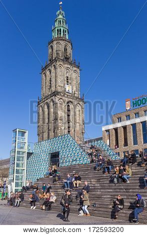 GRONINGEN, NETHERLANDS - FEBRUARY 15, 2017: People enjoying the spring sun in front of the Martini tower in Groningen, The Netherlands
