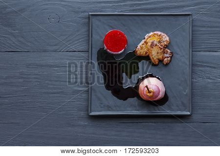 Restaurant dish of haute cuisine top view. Seared foie gras served with berry sauce and pink pear on black slate plate. French delicatessen meal, roasted goose liver. Copy space