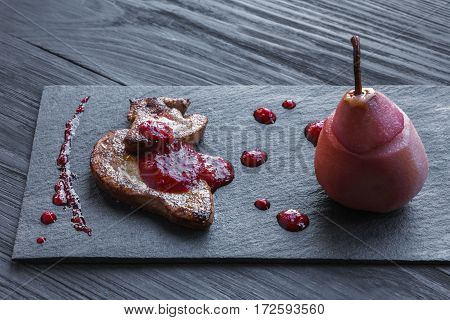 Creative french cuisine. Restaurant dish, seared foie gras served with berry sauce and pink pear on black slate plate. Delicatessen meal, roasted goose liver.