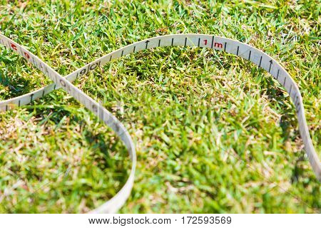 close up of sport measuring tape on grassy field showing 1 meter mark on sunny day