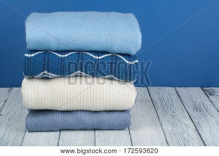 Knitted wool sweaters. Pile of knitted winter autumn clothes on blue wooden background sweaters knitwear space for text.