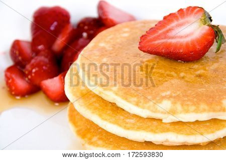 pancake with maple syrup and strawberries closeup