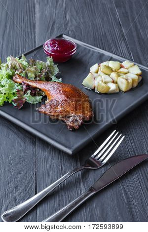 Roasted duck leg served with apples and cherry sauce. Restaurant food on black wood table. Vertical