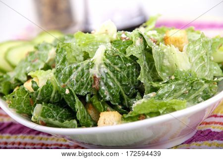 caesar salad closeup bowl with crouton and bacon