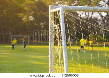 corner of a soccer or football goal post with warm morning light and blurred players and field in background