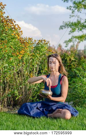A girl in blue dress with yoga bowl in her hads practicing yoga asanas and exercises on a green lawn in sunny summer day.