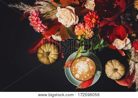 Cappuccino and beautiful flowers bouquet still life. Flower shop composition. Coffee cup, pumpkins on black wood background. Florist art and floral design concept, copy space on black, top view