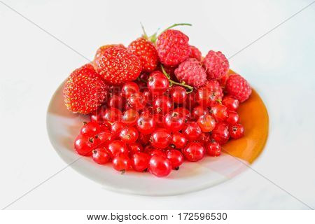 Berries red currants strawberries and raspberries on a plate. Ripe fruit. Close-up.
