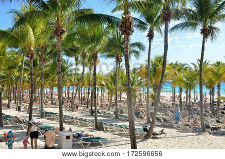 Playa del Carmen Mexico - January 28 2017: Crowded beach area with Palm trees