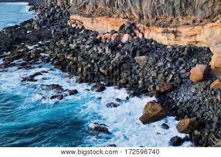 Top view of the sea and the waves crashing on the shore rocks in the sunlight. Tenerife, Canary Islands, Spain