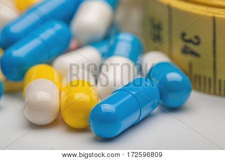 Measuring Tape And Medicines On White Background