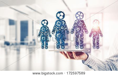 Close of businessman holding tablet pc with figures of family. Mixed media