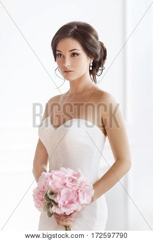 Beauty portrait of bride wearing wedding dress with feathers with luxury delight make-up and hairstyle, studio indoor photo. Young attractive multi-racial Asian Caucasian model with pink bouquet of flowers. Beautiful young woman like a bride isolated on w