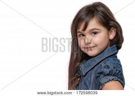 Portrait of long haired brunette little girl isolated on the white background. Girl is standing sideways and is looking at the camera. Free place for your text is in the left side of the photo.