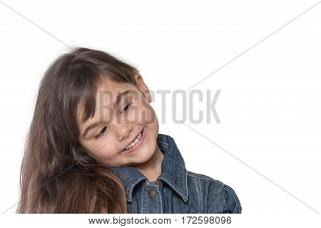 Portrait of long haired brunette little girl isolated on the white background. The girl has her head tilted and is looking into free place ready for your text.