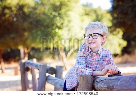 cute smiling boy student in glasses enjoying time outdoor back to school concept