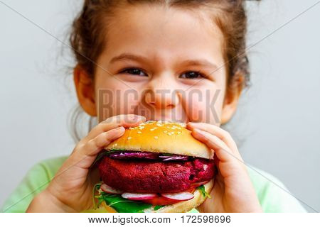 Happy hungry child (girl) eating healthy vegan burger.