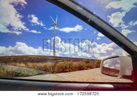 sunny blue sky on a windmill field from a window car