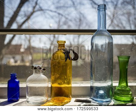Five colored bottles isolated over a window