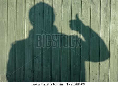 the shadow of a man against a green wooden wall gestures Suite