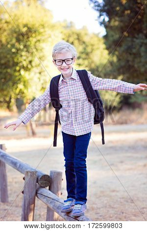 cute school boy student in glasses and with backpack enjoying time outdoor back to school concept