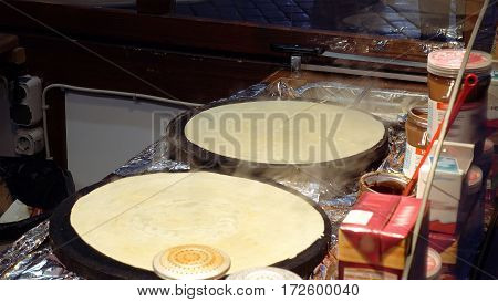 Hot sweet pancakes is being cooked on the street kitchen. Street food is popular for snack or lunch in big cities.