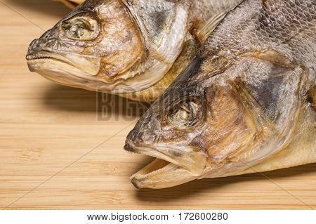 Salty dry river fish to beer on a wooden table. Macro shot.