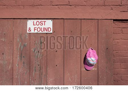 Pink cap hanging in a hook at lost and found