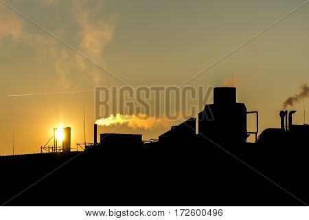 silhuette Industrial factory smoke from smokestacks over a colorful sunset sky industry