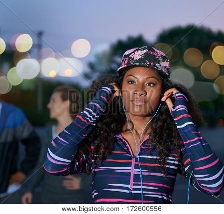 Flash photography portrait of trendy black hipster wearing a cap ready for night jogging with her running group in an urban background with bokeh lights