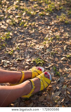 Closeup of woman's feet in bright yellow sandals on the ground. Sunny summer day outdoors. woman walking in the park.