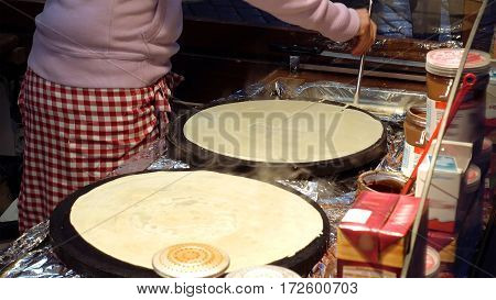 Cooking hot sweet pancakes on the street kitchen. Street food is popular for snack or lunch in big cities.