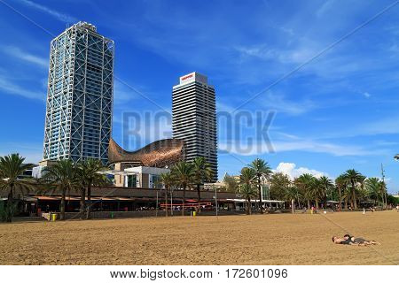 BARCELONA/ SPAIN - SEPTEMBER 29. City beach Playa del Somorrostro and modern buildings (Hotel Arts Barcelona, construction floating fish and Mapfre Tower) on September 29, 2014. Barcelona, Spain