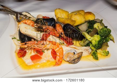 Varied seafood dorade mussels and shrimps on a white plate.