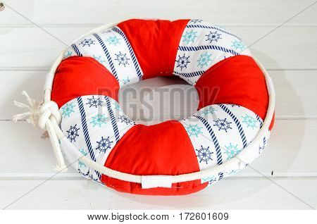 Lifebuoy handmade pillow on white wooden table with copyspace