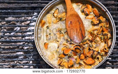 Purified from the shells of sea mussels simmer in a creamy sauce over an open fire outdoors.